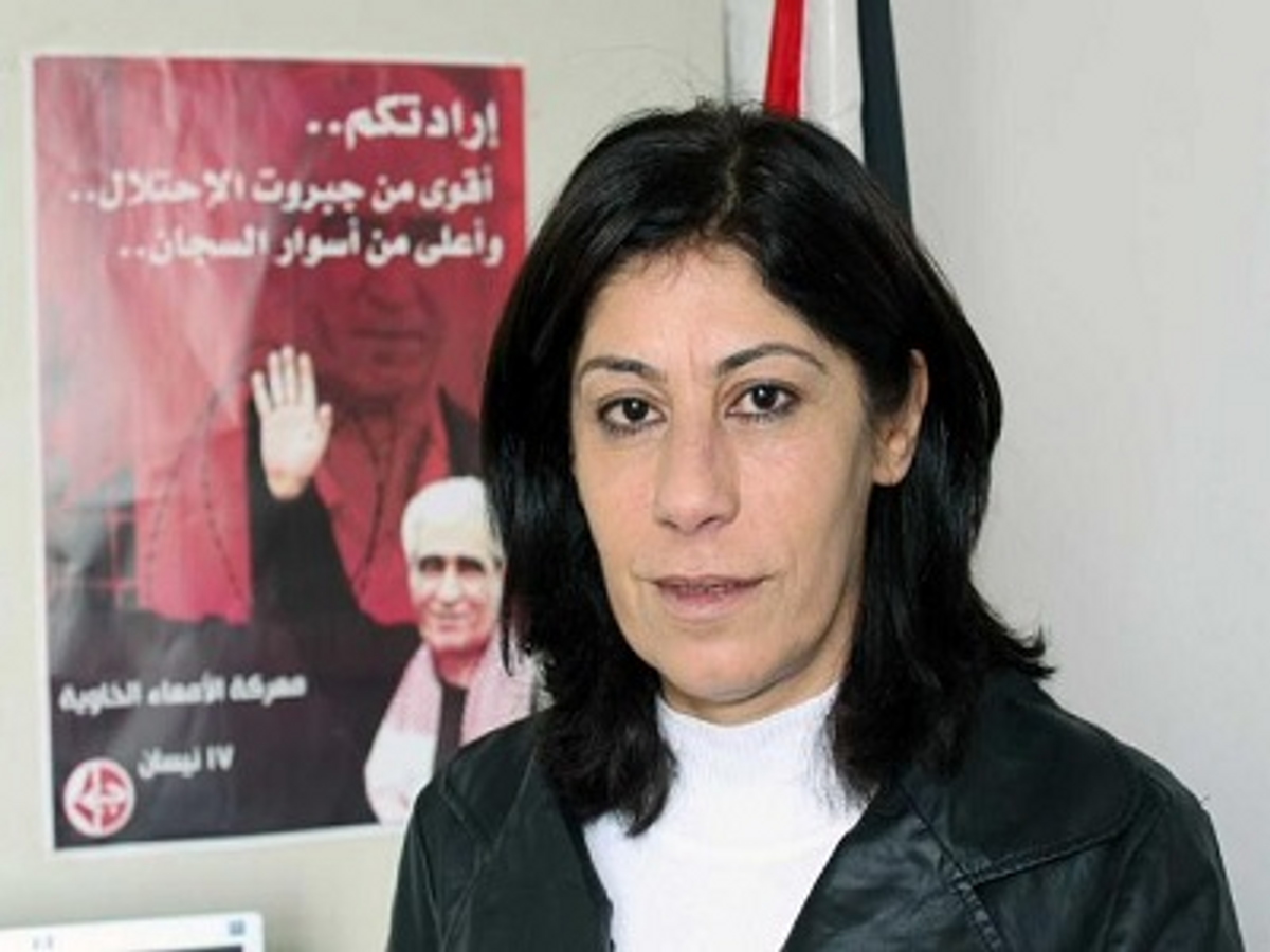 Khalida Jarrar posing with PFLP poster featuring the             imprisoned terrorist Ahmad Sa�adat, convicted of plotting             the 2001 murder of Israeli Tourism Minister Rehavam Ze�evi